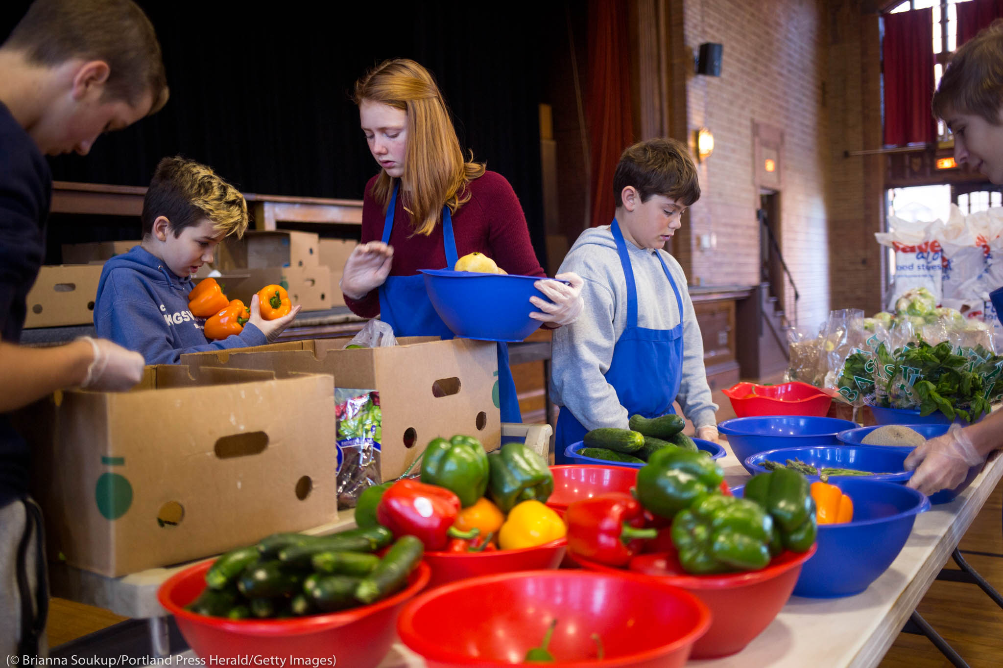 Young people working with containers of food (© Brianna Soukup/Portland Press Herald/Getty Images)