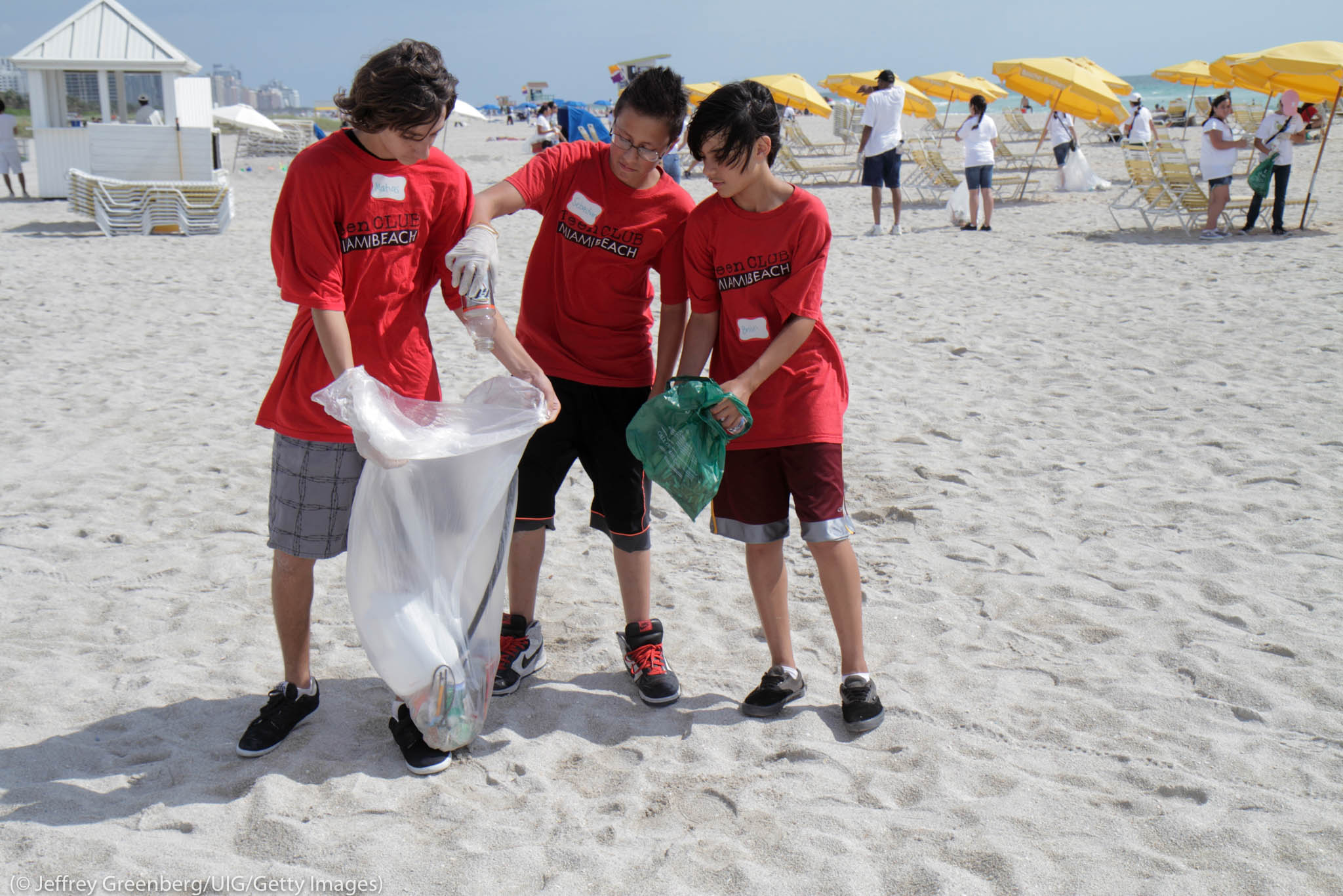 Young people collecting trash on beach (©Jeffrey Greenberg/UIG/Getty Images)