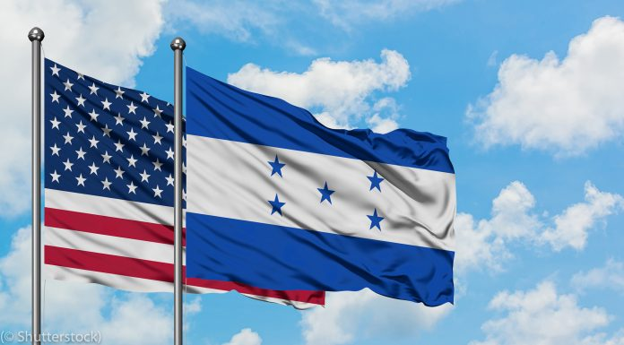 United States and Honduras flags with sky with clouds background (© Shutterstock)