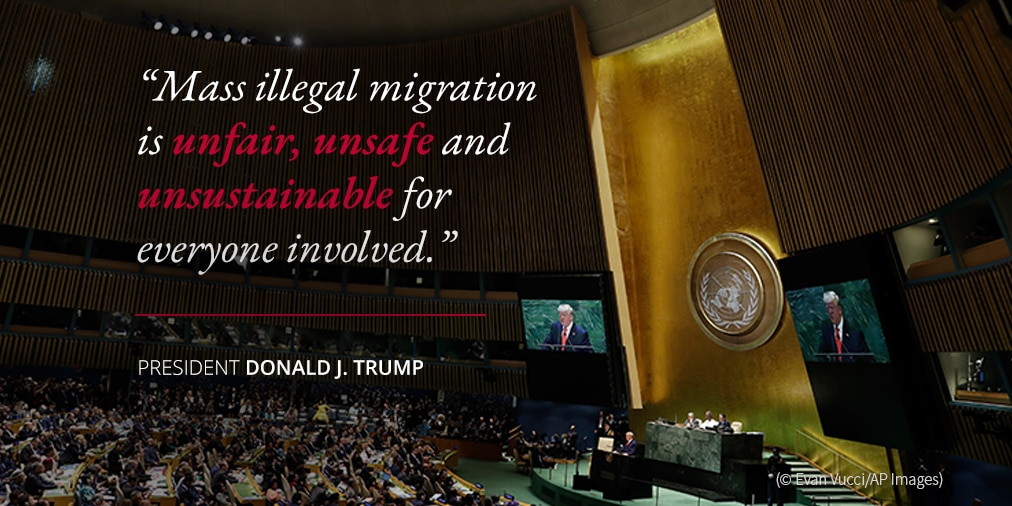 President Trump on dangers of illegal migration; photo of crowd in auditorium (© Evan Vucci/AP Images)