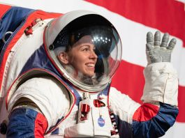 Woman in spacesuit waving (NASA/Joel Kowsky)