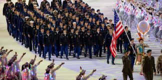 Military members marching in formation behind U.S. flag (Dept. of Defense/E.J. Hersom)