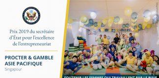 Photo d'hommes, de femmes et de jeunes enfants dans une pièce, des ballons flottant au plafond et une citation sur le prix d'excellence de l'entrepreneuriat (Département d'État)