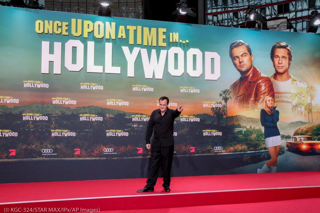 Quentin Tarantino parado frente al anuncio de una película (© KGC-324/STAR MAX/IPx/AP Images)