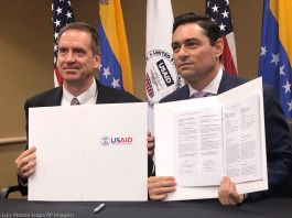 Two men holding up signed agreements (© Luis Alonso Lugo/AP Images)