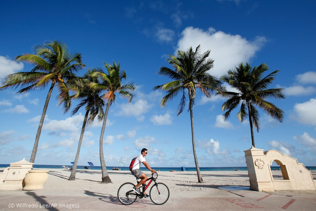 Person biking past beach with palm trees and low, white walls (© Wilfredo Lee/AP Images)