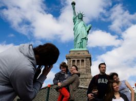 Tourists posing in front of the Statue of Liberty (© John Minchillo/AP Images)