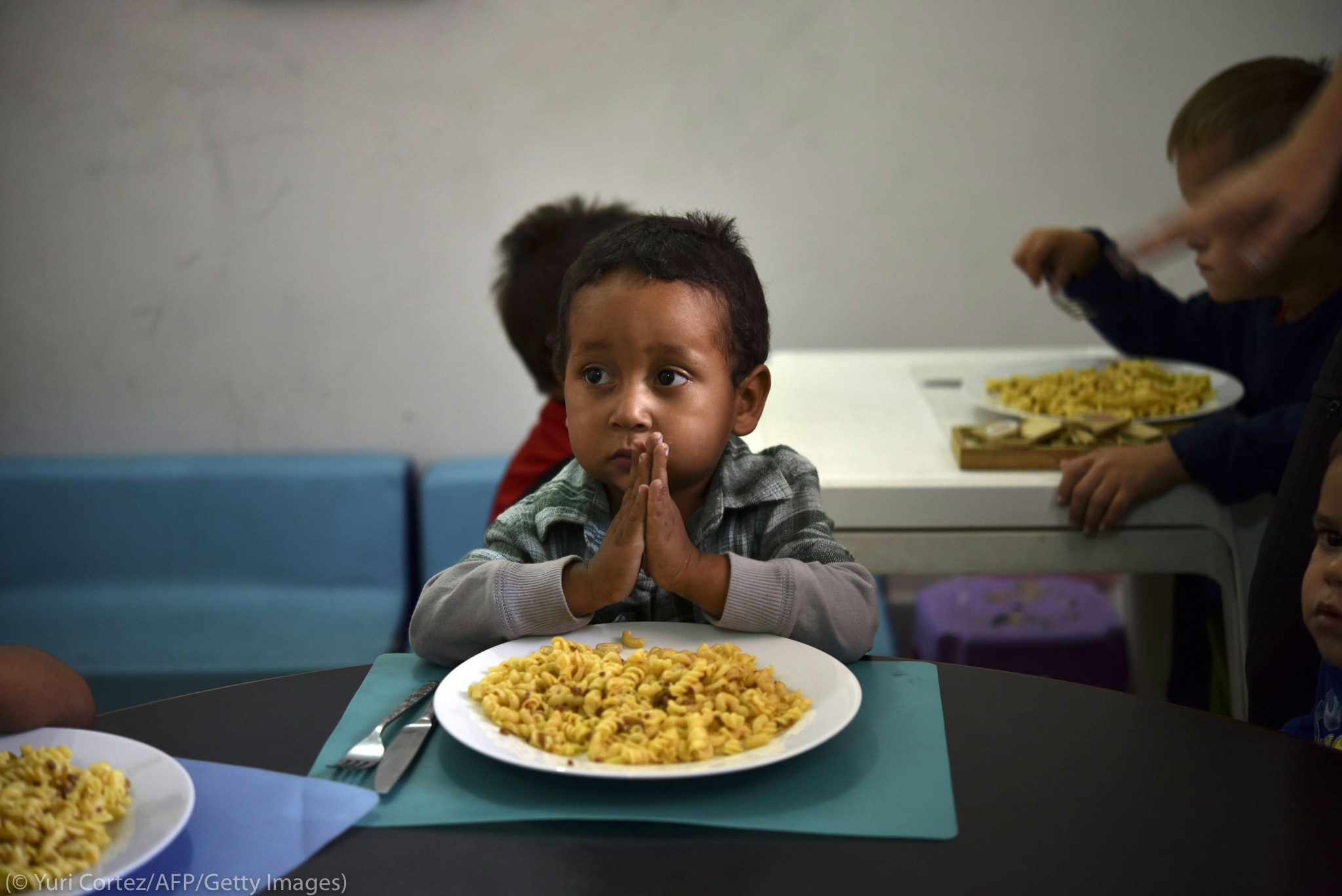 Child praying before eating (©Yuri Cortez/AFP/Getty Images)