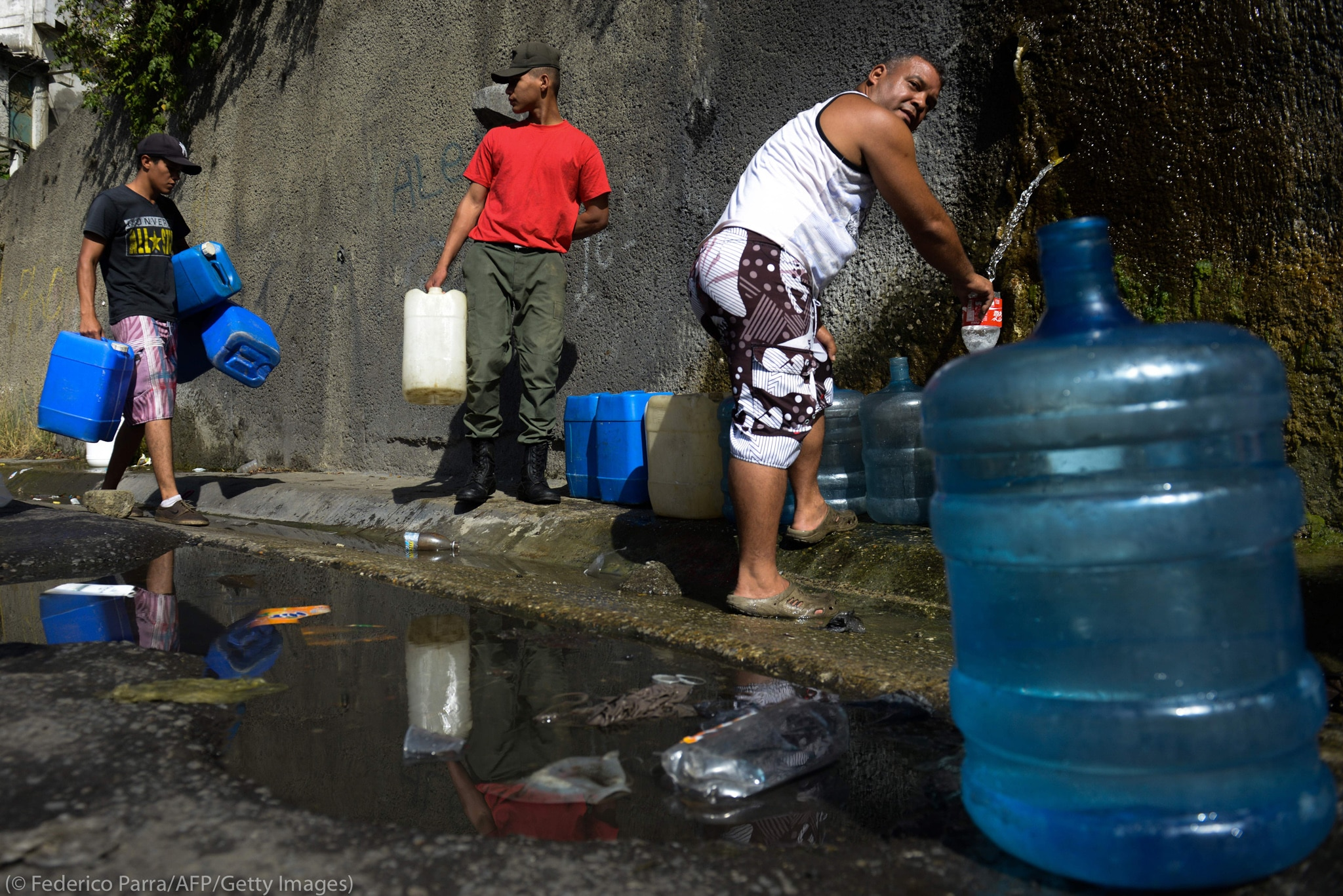 People filling jerrycans with water (© Federico Parra/AFP/Getty Images)