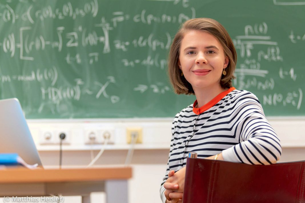 Woman seated in front of blackboard (©Matthias Heisler)