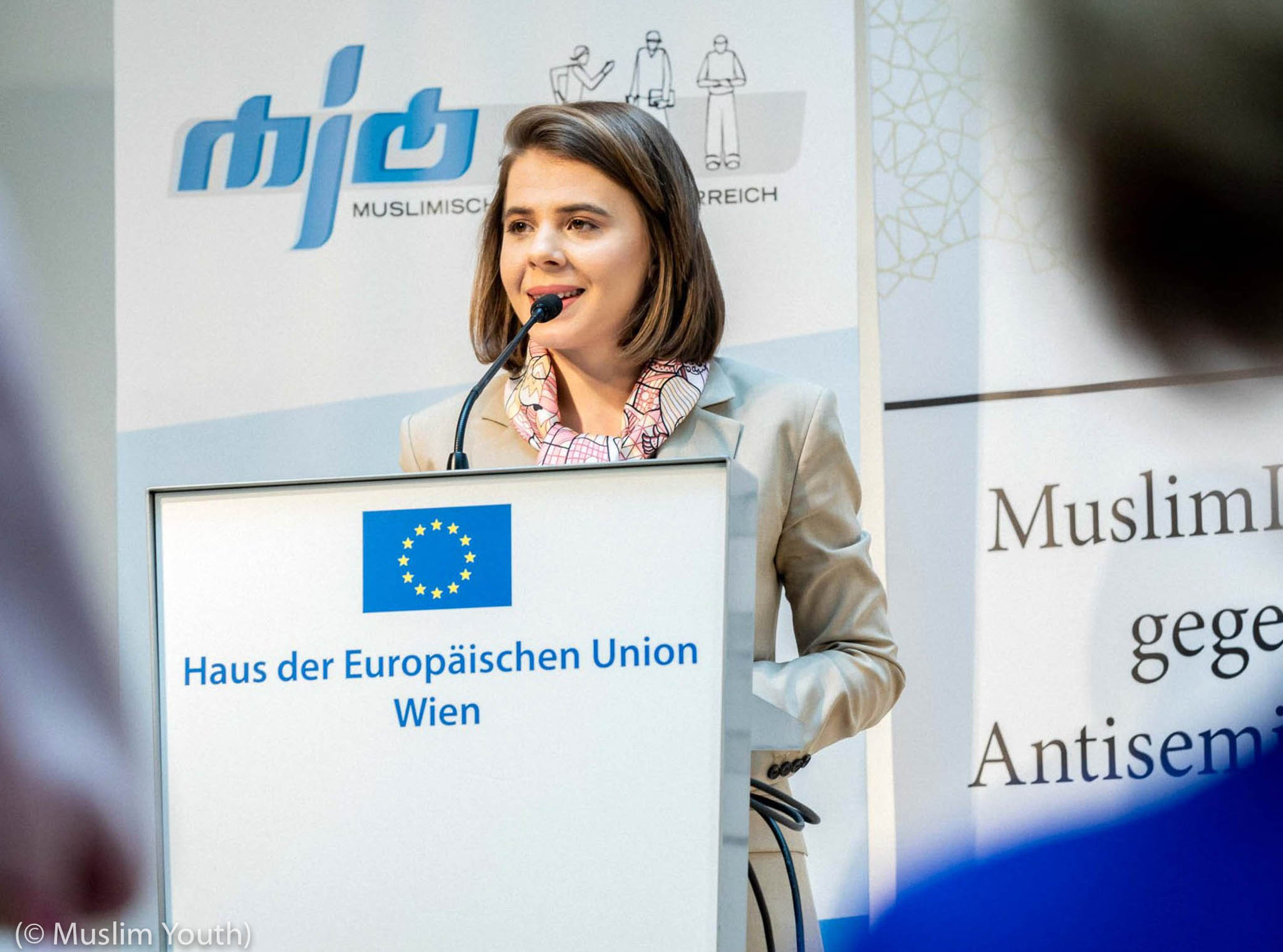 Woman at lectern with microphone (© Muslim Youth)