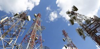 Vue en contre-plongée de tours de télécommunications avec le ciel bleu et quelques nuages en arrière-plan (© Sattaya/Shutterstock)