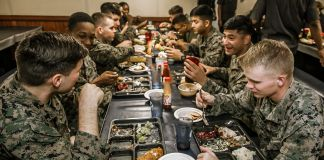 Long table of soldiers eating a meal and talking and laughing (U.S. Marine Corps/Staff Sgt. Dengrier M. Baez)