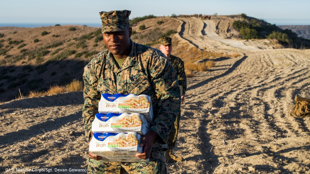 Two soldiers carrying packages of food while marching along a long dirt road (U.S. Marine Corps/Sgt. Devan Gowans)