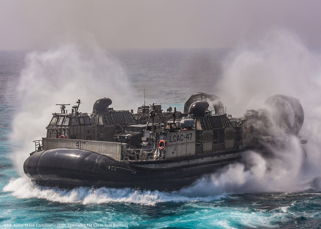 Military craft with large cushion on bottom in water, surrounded by mist and waves (U.S. Navy/Mass Communication Specialist 1st Class Toni Burton)
