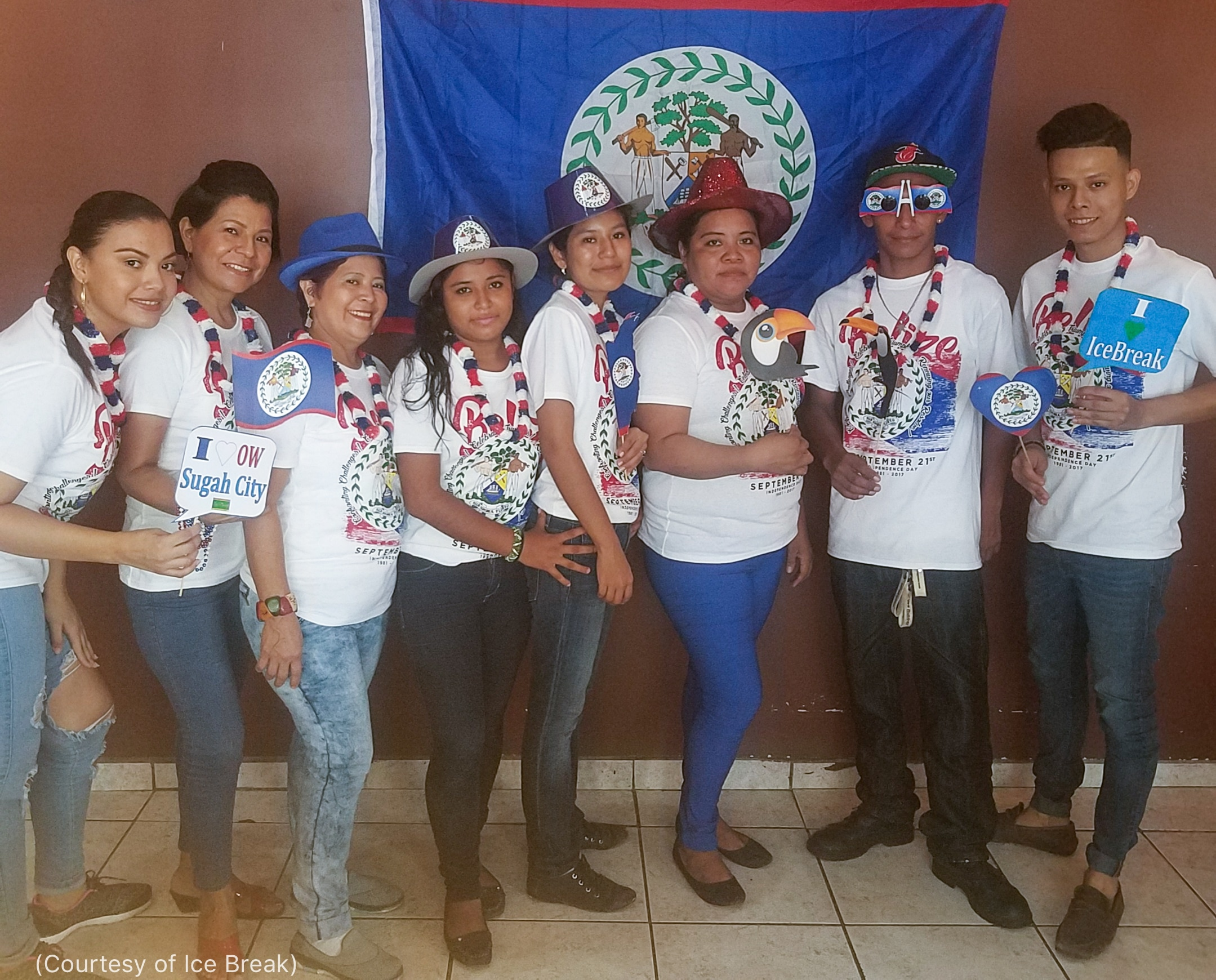 Line of people posing by flag of Belize (Courtesy of Ice Break)