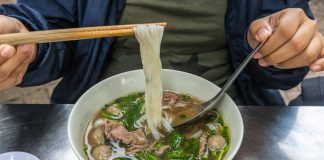 Diner holding noodles over bowl with chopsticks (© Quang Ngo/Alamy Stock Photo)