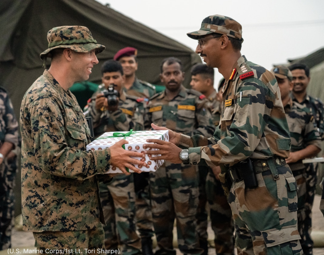 Soldier handing wrapped gift to another service member (U.S. Marine Corps/1st Lieutenant Tori Sharpe)