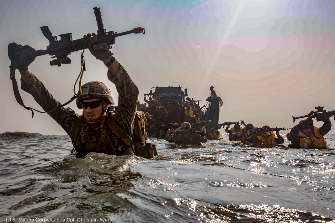 Service members walking through chest-high seawater holding weapons aloft (U.S. Marine Corps/Lance Corporal Christian Ayers)