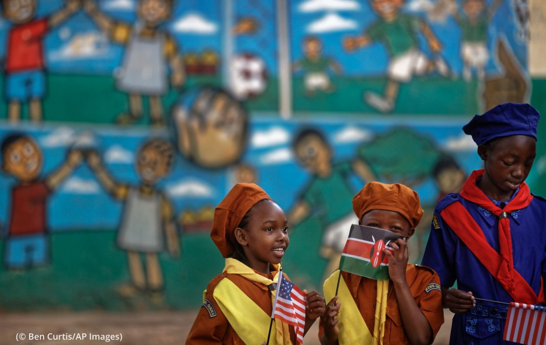 Three young girls holding flags in front of wall holding cartoon (© Ben Curtis/AP Images)
