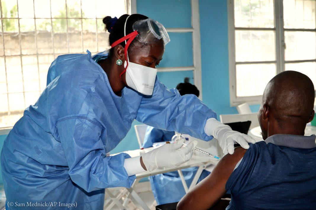 ہاتھوں پر دستانے پہنے اور منہ پر ماسک لگائے ایک عورت ٹیکہ لگا رہی ہے۔ (© Sam Mednick/AP Images)