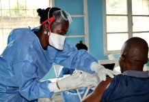 Une soignante portant des gants et un masque faisant une piqûre dans le bras (© Sam Mednick/AP Images)