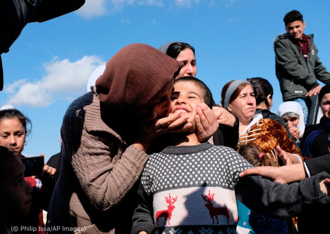 People standing near woman kissing smiling child (© Philip Issa/AP Images)