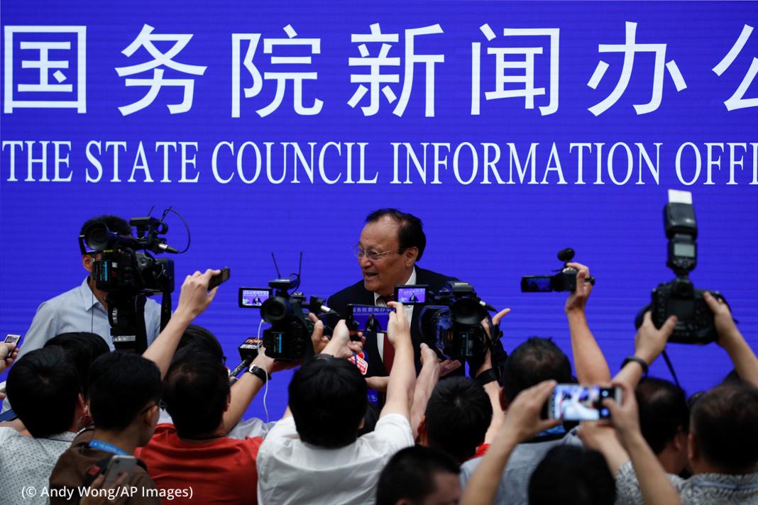 Reporteros que se acercan a un hombre que habla (© Andy Wong/AP Images)
