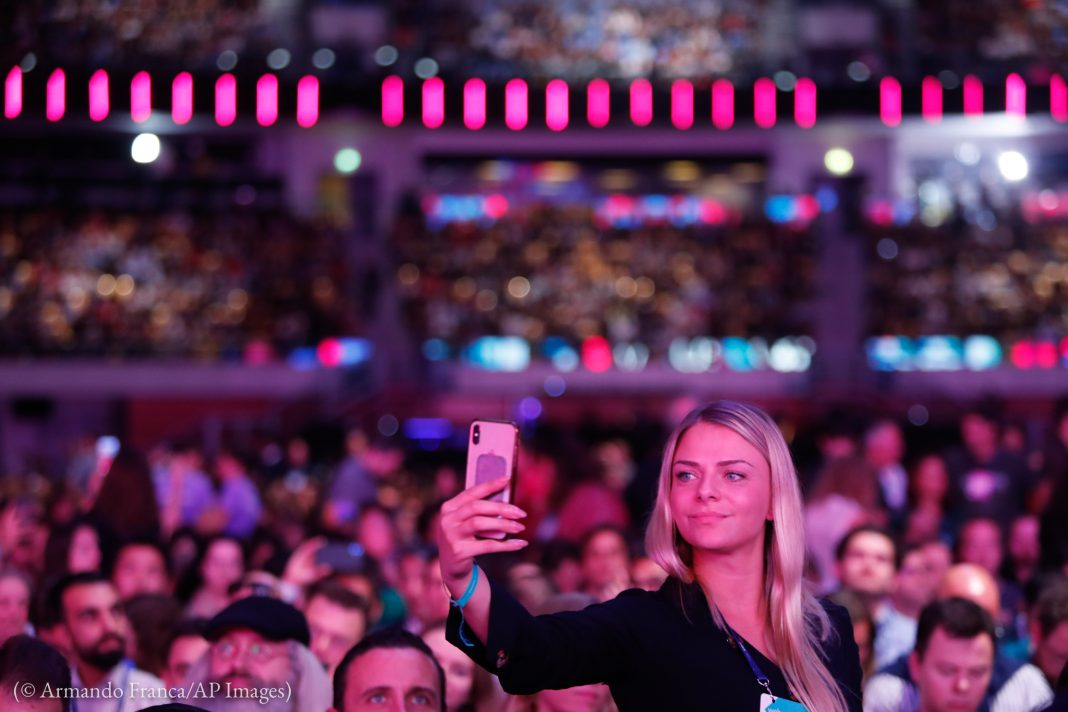 Woman taking video of large crowd in arena (© Armando Franca/AP Images)