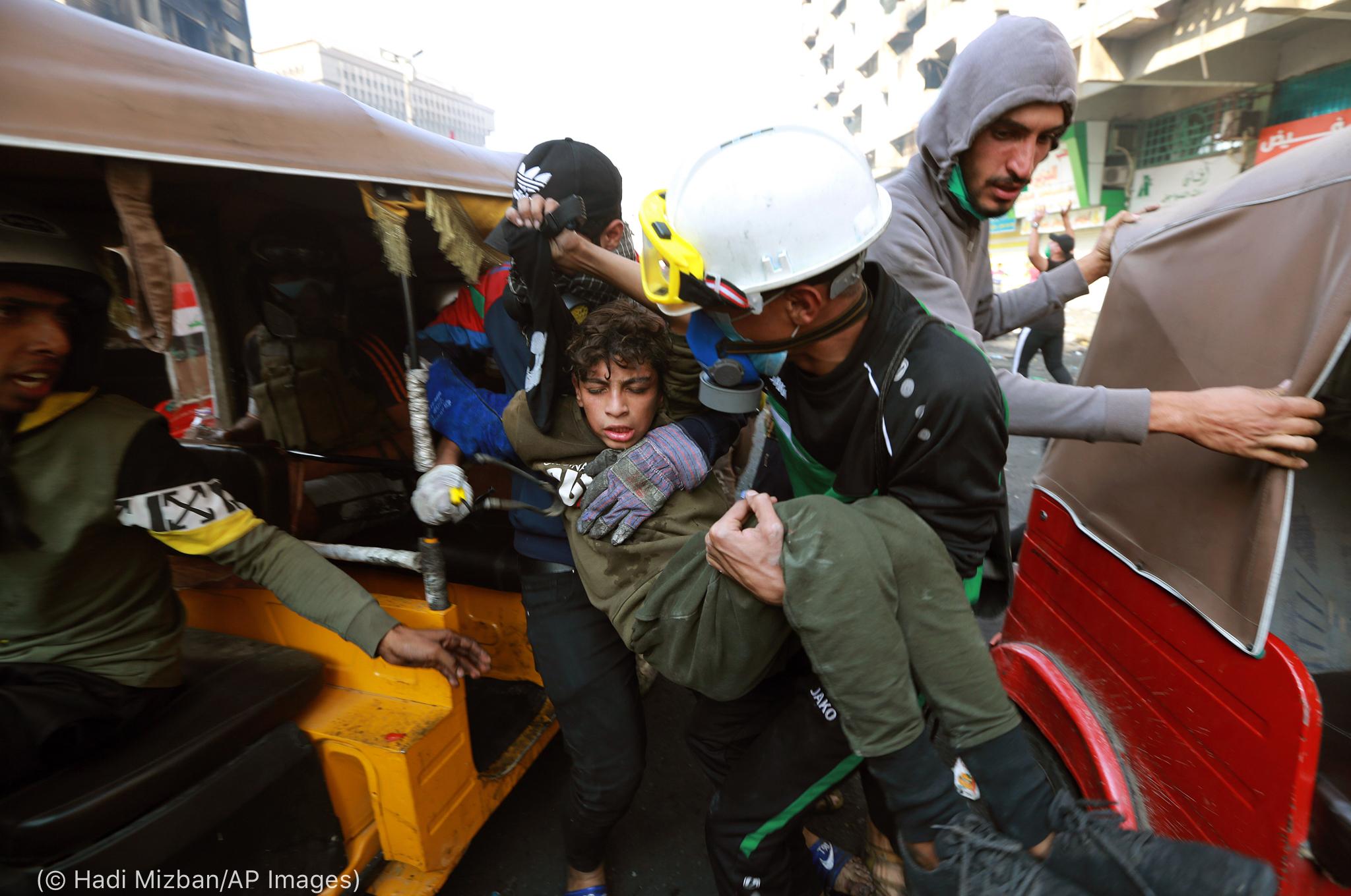 Homem carrega menino nos braços (© Hadi Mizban/AP Images)