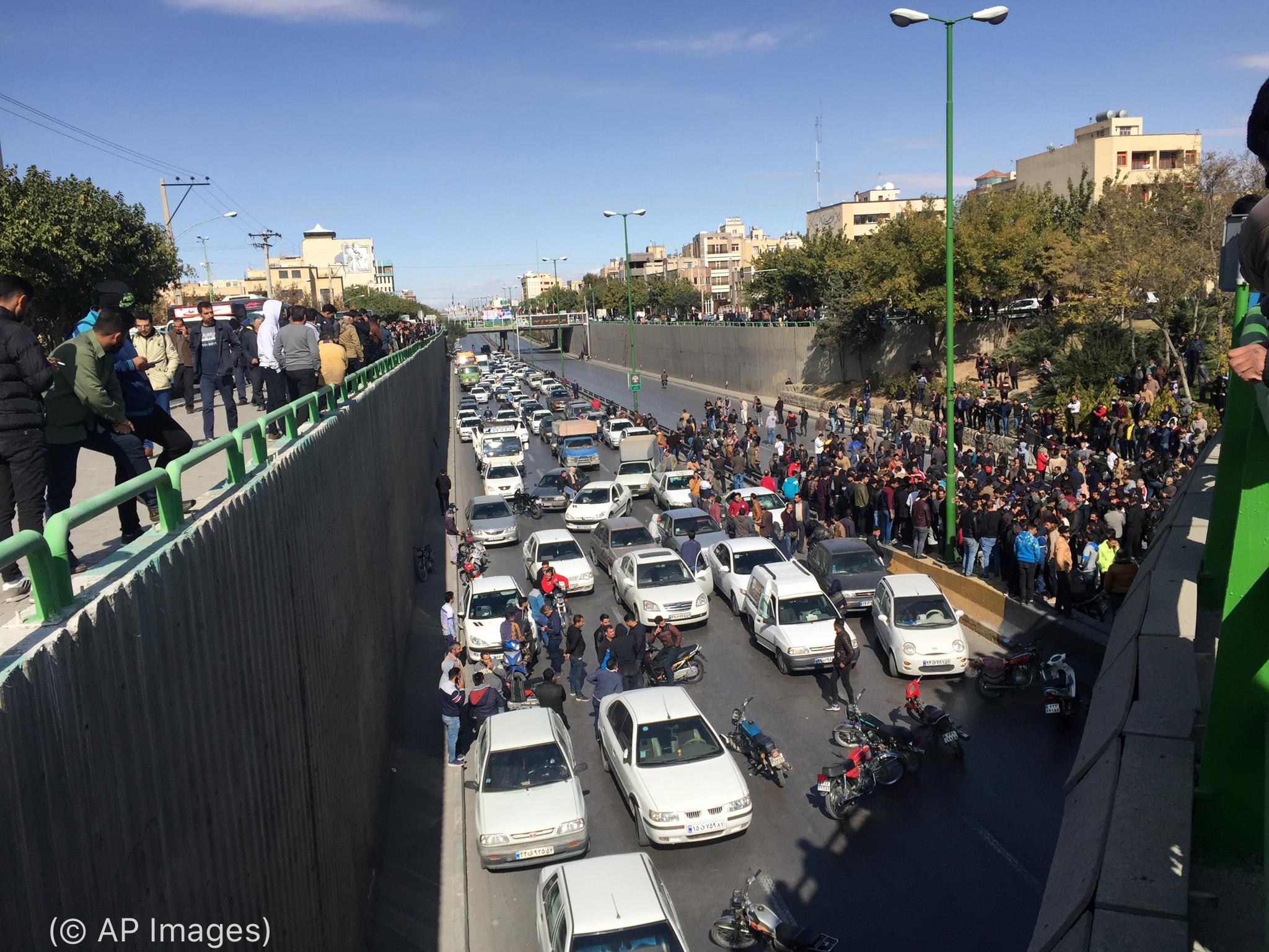 Carros parados e pessoas em pé na rua (© AP Images)