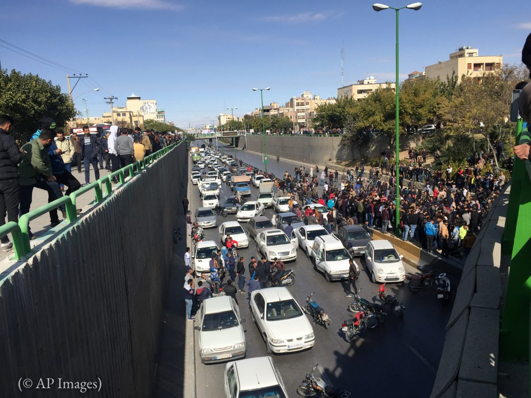 Protesters blocking road with cars in Iran