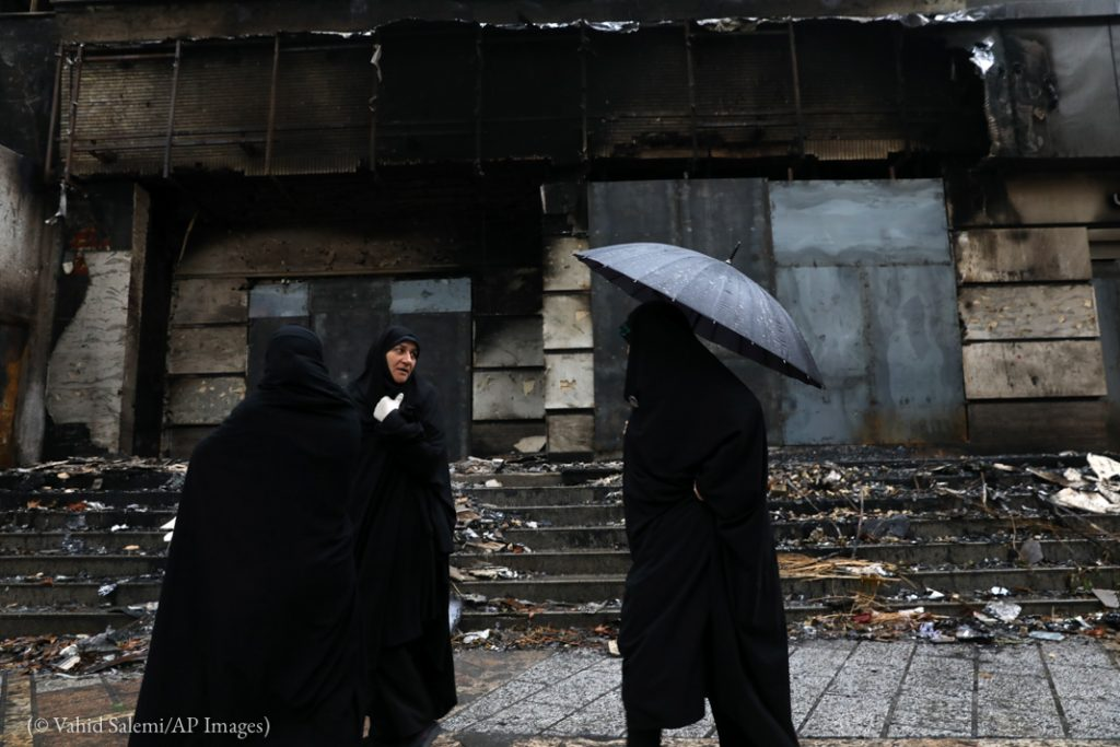 Trois femmes passant devant un bâtiment endommagé (© Vahid Salemi/AP Images)