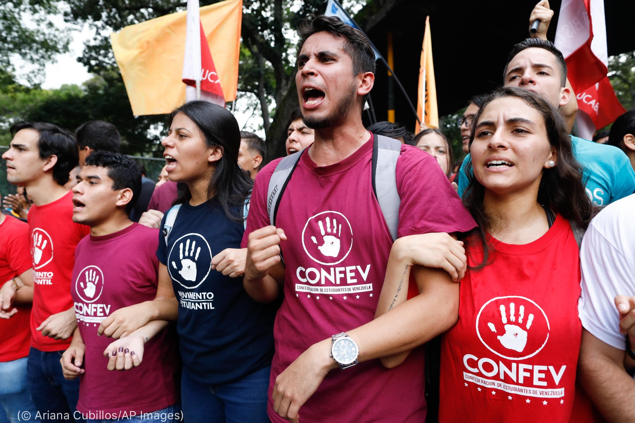 Jovens em pé protestam de braços dados (© Ariana Cubillos/AP Images)