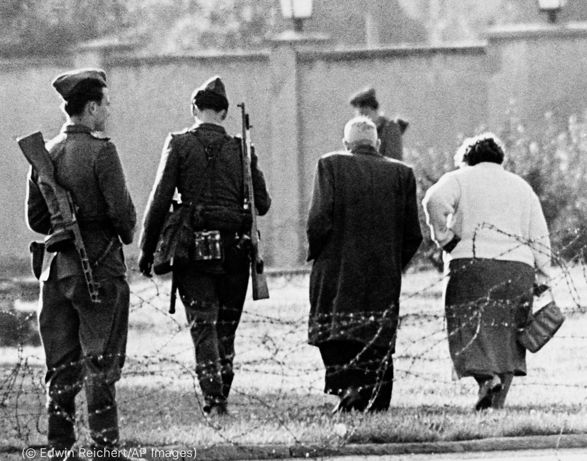 Un couple s'éloignant, accompagné par un soldat (© Edwin Reichert/AP Images)