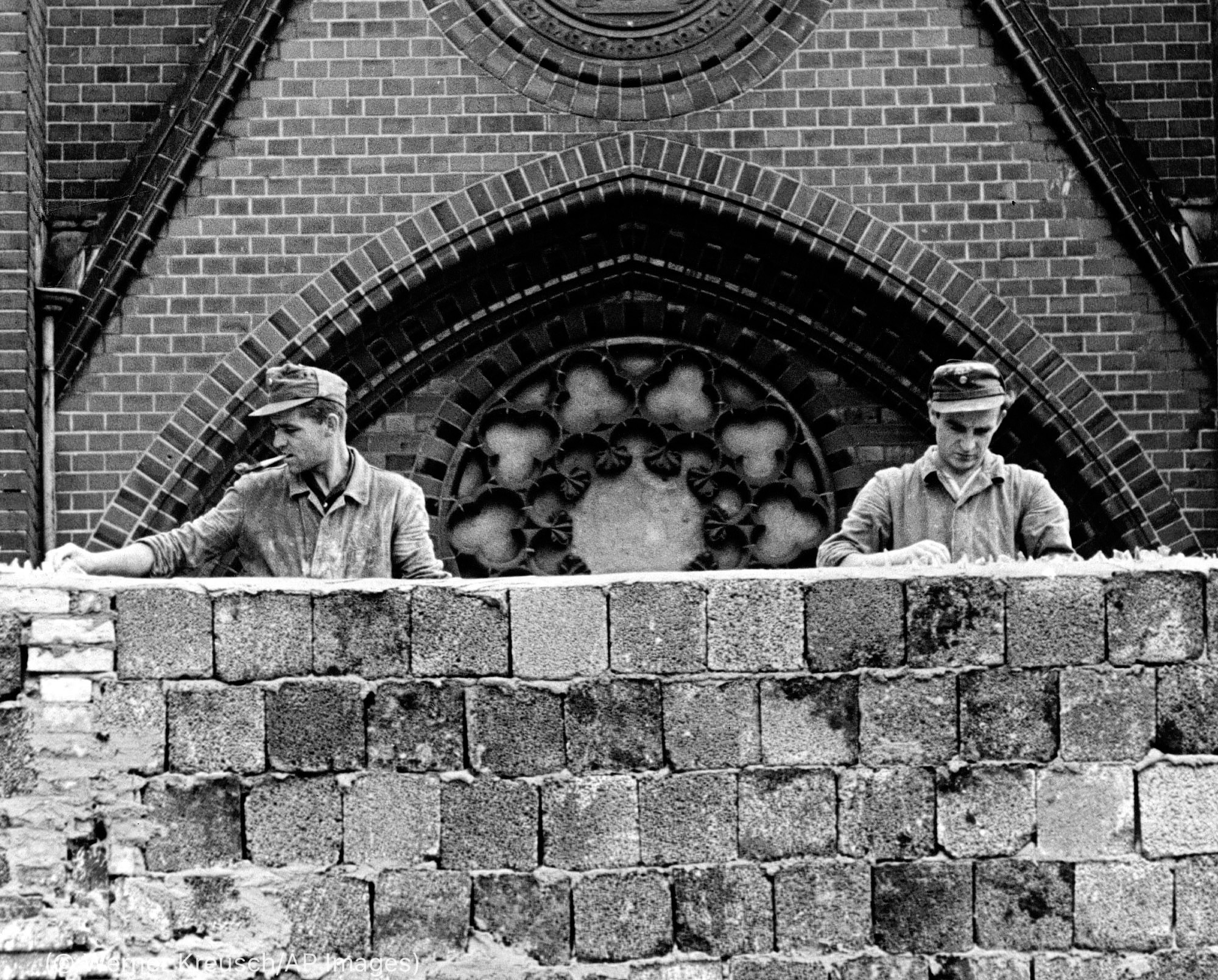 Uniformed men placing glass on top of concrete wall (© Werner Kreusch/AP Images)