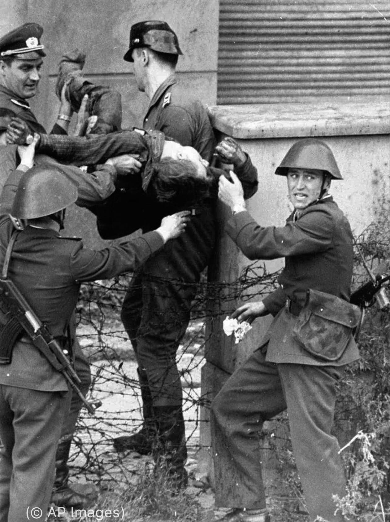 Des hommes en uniforme transportant un homme par-dessus une clôture de barbelés (© AP Images)