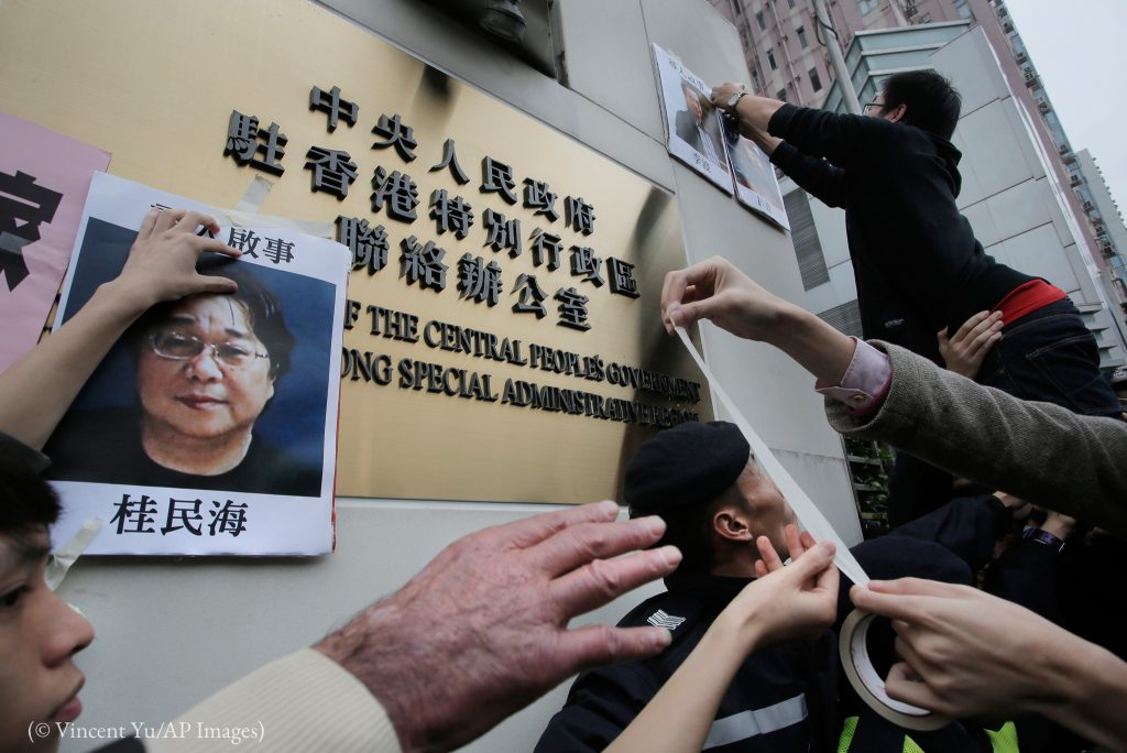 Person trying to put up poster (© Vincent Yu/AP Images)