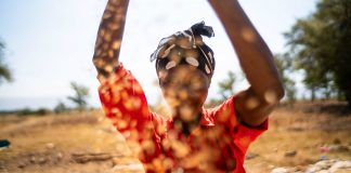 Woman throwing rice in the air (Nevil Jackson/USAID)