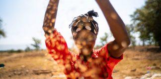 Le visage d'une femme les deux bras levés avec un champ agricole et des arbres en arrière-plan (Nevil Jackson/USAID)