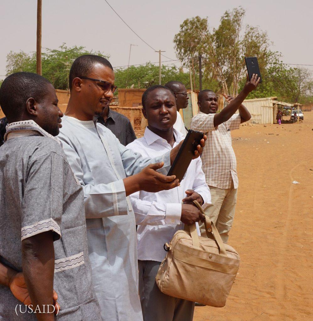 Des hommes debout à l'extérieur d'un dispensaire, en train de regarder leurs tablettes (USAID)