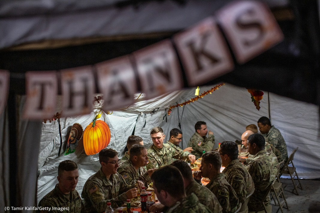 Men sitting at table (© Tamir Kalifa/Getty Images)