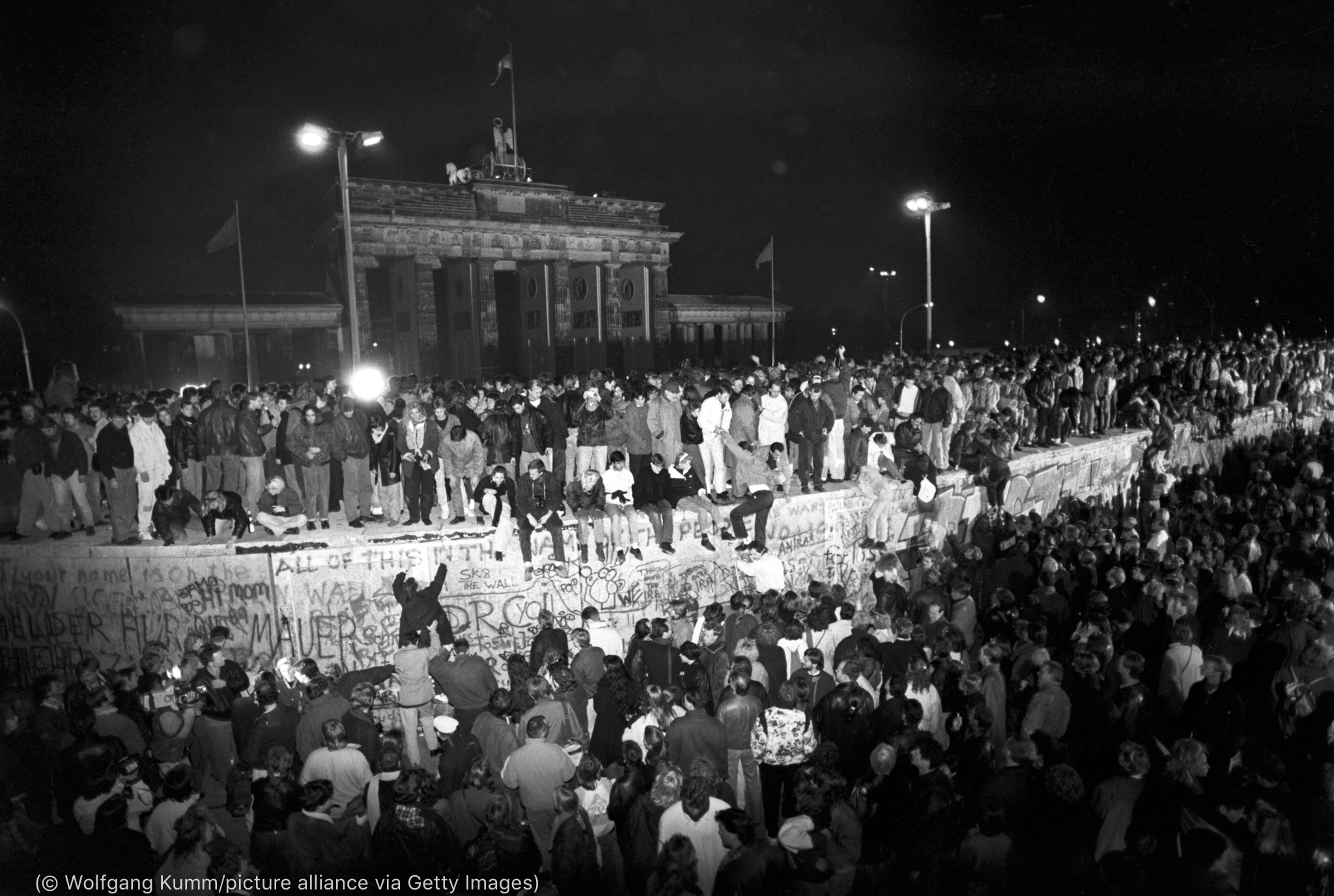 Large crowd celebrating at wall, with members standing on top (© Wolfgang Kumm/picture alliance via Getty Images)