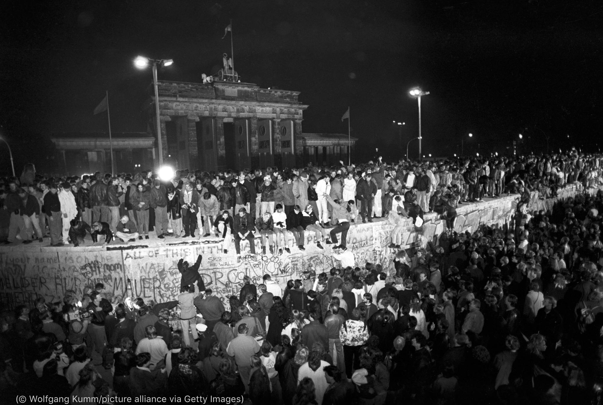 Une grande foule en liesse devant le mur de Berlin, avec de nombreuses personnes debout sur le mur (© Wolfgang Kumm/picture alliance via Getty Images)