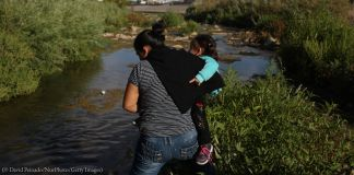 Woman carrying child crossing a river (© David Peinado/NurPhoto/Getty Images