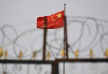 Bendera China di balik pagar berduri di salah satu kamp di Xinjiang tempat umat Muslim ditahan dengan dalih mencegah terorisme. (© Gred Baker/AFP/Getty Images)