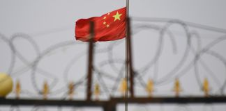 Chinese flag behind razor wire (© Gred Baker/AFP/Getty Images)