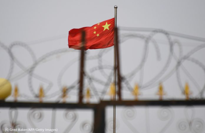 Flag seen behind razor wire (© Gred Baker/AFP/Getty Images)