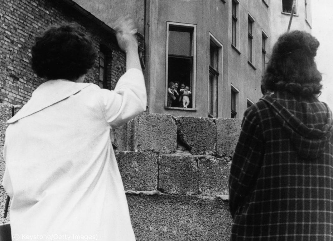 Des personnes se saluant par-dessus un mur (© Keystone/Getty Images)
