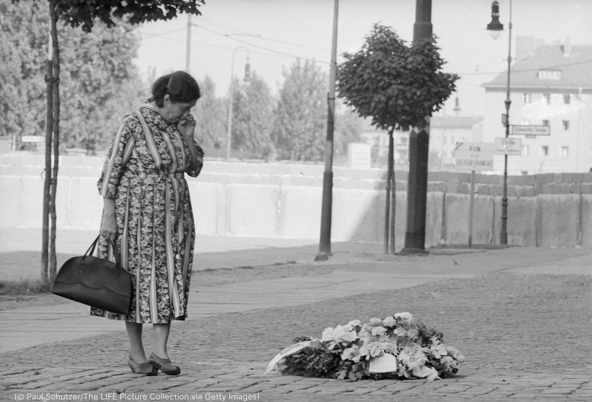 Woman mourning at pile of flowers in street (© Paul Schutzer/LIFE Picture Collection via Getty Images)
